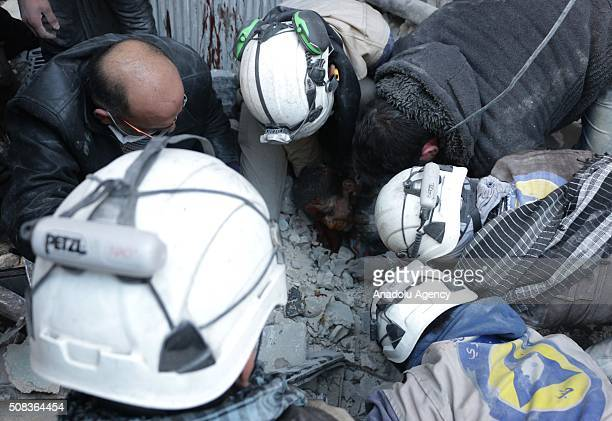 Civil defense team members pull out a boy from debris as they try to search casualties after the war crafts belonging to the Russian army carried out...