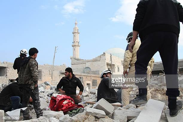 Civil defense team members try to rescue the Syrians who were buried under the wreckage after the war crafts belonging to the Russian Army carried...