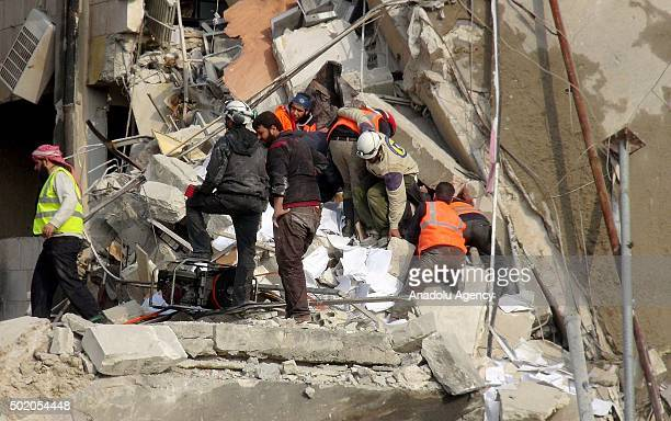 Civil defense team members try to search casualties among the destroyed buildings after the warcrafts belonging to the Russian army carried out...