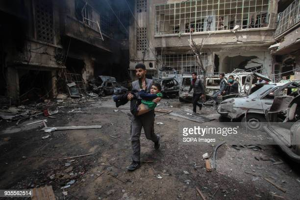 A civil defense volunteer carrying an injured child outside a building where other 7 residents died General view of the aftermath of the air strikes...