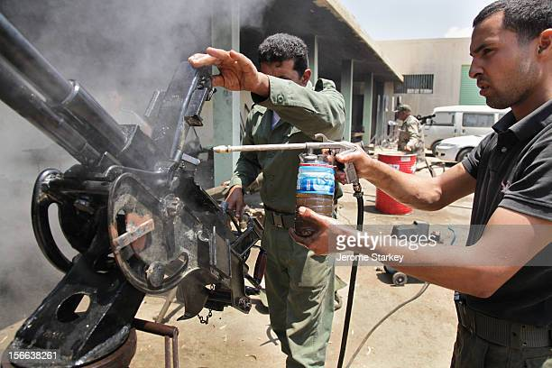 Civil engineer Ahmed Ali and Abdul Baset elTashani inspect a Russian made DShK machinegun after repairing the firing mechanisms and rewelding it on...