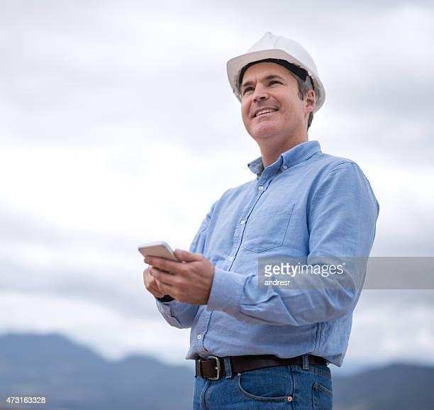 Ingeniero Civil enviando mensajes de texto en su teléfono