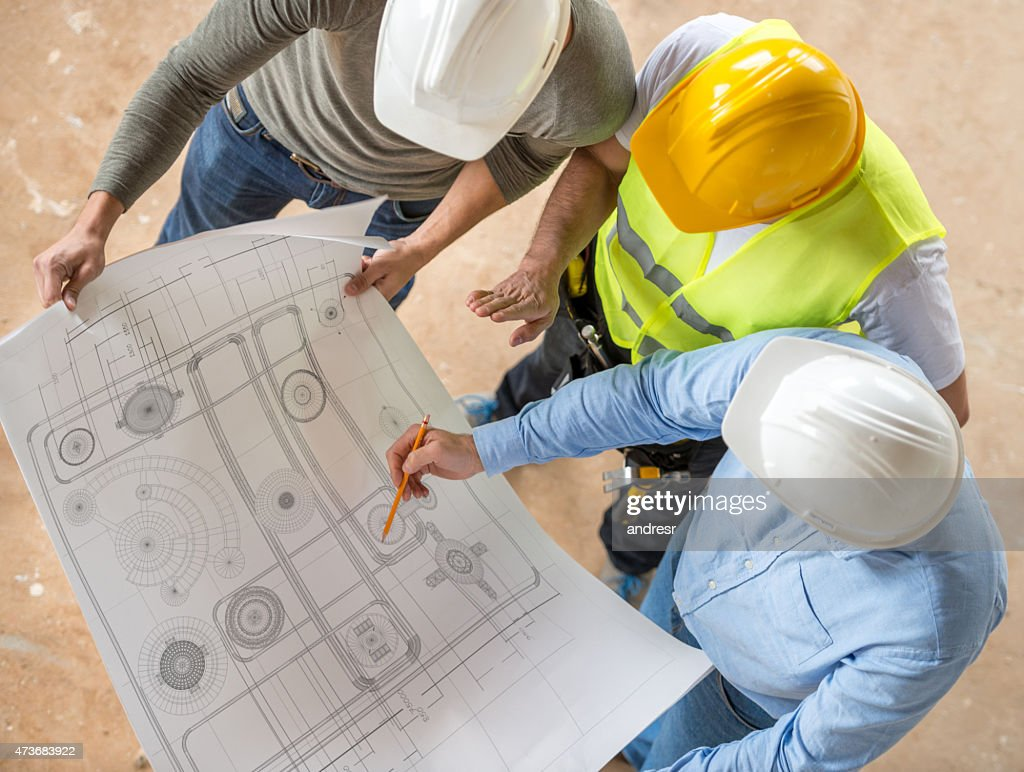 Civil engineers looking at blueprints : Stock Photo