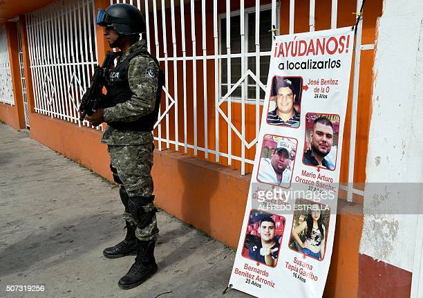 A Civil Forces police stands next to a banner with pictures of five youngsters who went missing past January 11 in Tierra Blanca community Veracruz...