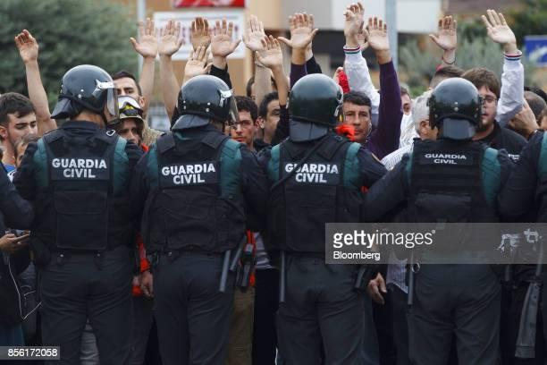 Civil Guard officers face members of the public outside a polling station used for the banned referendum in Sant Julia de Ramis Spain on Sunday Oct 1...