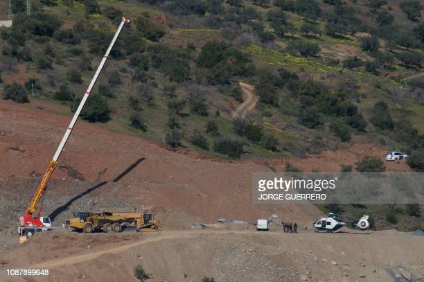 A Civil Guard's helicopter is pictured next to a crane at the site where a child fell down a well in Totalan southern Spain on January 24 2019...