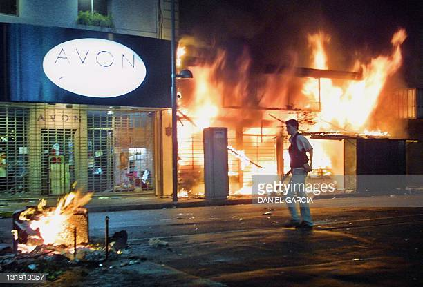 A civil police officer walks in front of storefronts that have been set on fire during the riots in Buenos Aires 20 December 2001 Four people were...