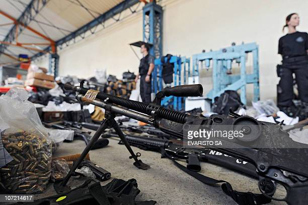Civil Police officers stand on November 30 2010 in Rio de Janeiro Brazil next to weapons seized during a raid at Morro do Alemao shantytown A total...