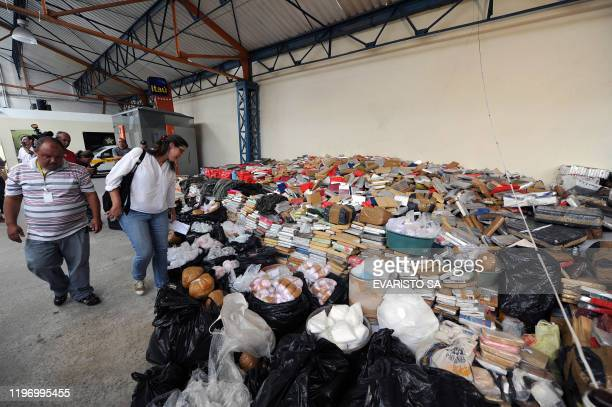 Civil Police officers stand on November 30 2010 in Rio de Janeiro Brazil next to drugs seized during a raid at Morro do Alemao shantytown A total of...