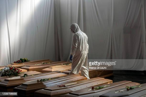 Civil Protection member is seen in the hangar where 18 coffins of victims of COVID-19 wait to be transported to Florence by the Italian Army to be...