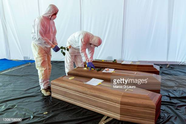 Civil Protection member rest a flower on the coffin of a victim of COVID-19 in the hangar where 18 coffins wait to be transported to Florence by the...
