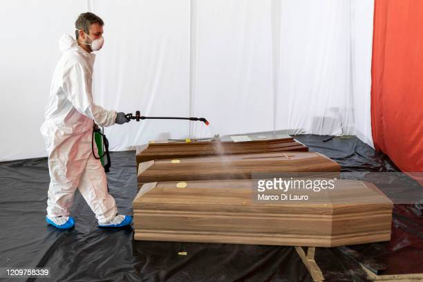 Civil Protection member sanitizes the coffin of a victim of COVID-19 in the hangar where 18 coffins wait to be transported to Florence by the Italian...