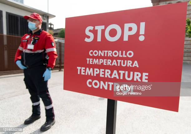 A civil protection member stands guard at the entrance of the new COVID19 Hospital at the OGR Officine Grandi Riparazioni on April 18 2020 in Turin...