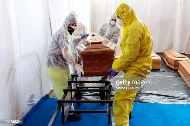 Civil Protection members and Carabinieri, Italian Paramilitary Police Officers, move one of 18 coffins of victims of COVID-19 to travel to Florence...
