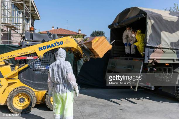 Civil Protection members and Carabinieri, Italian Paramilitary Police Officers move one of 18 coffins of victims of COVID-19 to an Italian Army truck...