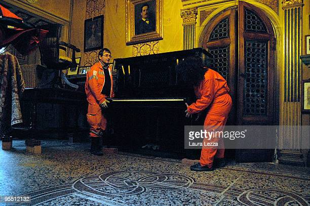 Civil Protection volunteers move a piano and items of furniture onto raised blocks to safeguard them in case of flooding inside Museo Villa Puccini...