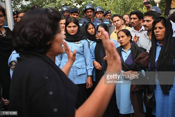 A civil rights activist asks policewomen not to arrest demonstrators at an antigovernment protest on November 4 2007 in Islamabad Pakistan A small...