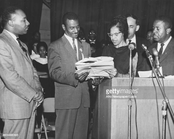 Civil rights activist Fred Shuttlesworth second from left receives a Southern Christian Leadership Conference citation from Rosa Parks as Dr Martin...