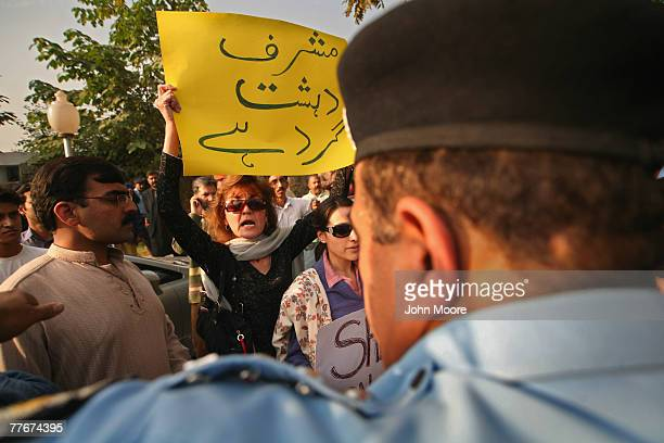 A civil rights activist holds a sign reading Musharraf is a terrorist at an antigovernment protest on November 4 2007 in Islamabad Pakistan A small...