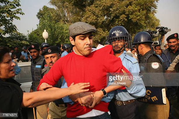 A civil rights activist is detained at an antigovernment protest on November 4 2007 in Islamabad Pakistan A small group of protesters held signs and...