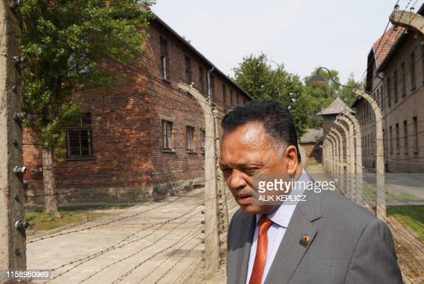 US civil rights activist Jesse Jackson walks between barbed wire fences as he visits the memorial site of the former AuschwitzBirkenau German Nazi...
