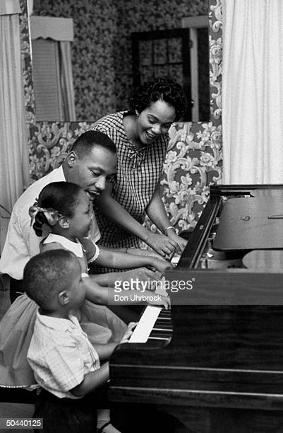 Civil Rights activist Rev Dr Martin Luther King Jr and his wife Coretta daughter Yolanda Martin Luther III sitting together as they play piano in...