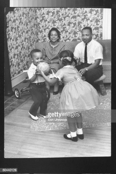 Civil Rights activist Rev Dr Martin Luther King Jr and his wife Coretta watching their son Martin Luther III pass a ball to his sister Yolanda while...