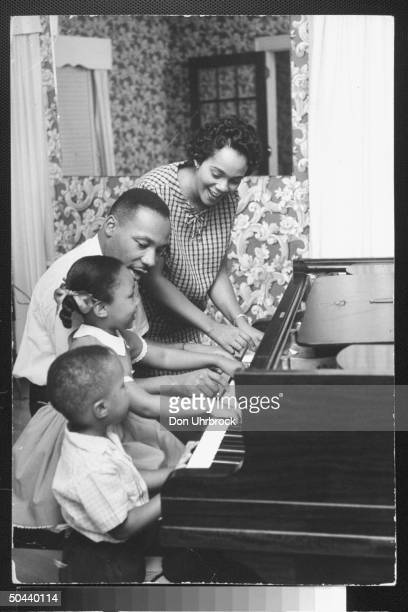 Civil Rights activist Rev Dr Martin Luther King Jr with his wife Coretta daughter Yolanda and Martin Luther III sitting together as they play piano...