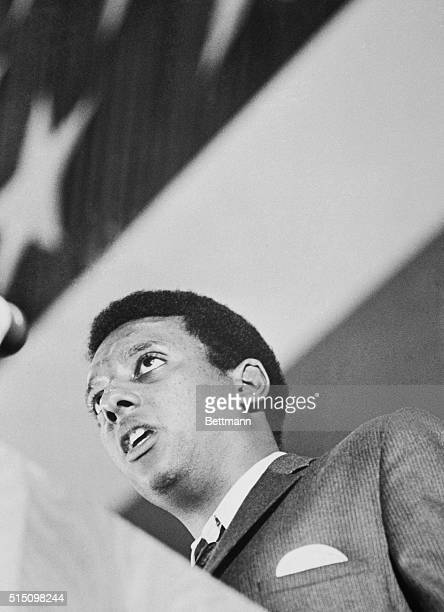 "Civil rights activist Stokely Carmichael stands beneath a massive American flag as he addresses a crowd attending Vanderbilt University's ""Impact""..."