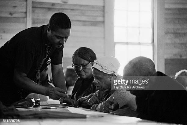 A civil rights activist teaches elderly black voters how to fill out their voting ballot so they wouldn't be disqualified Civil rights groups held...