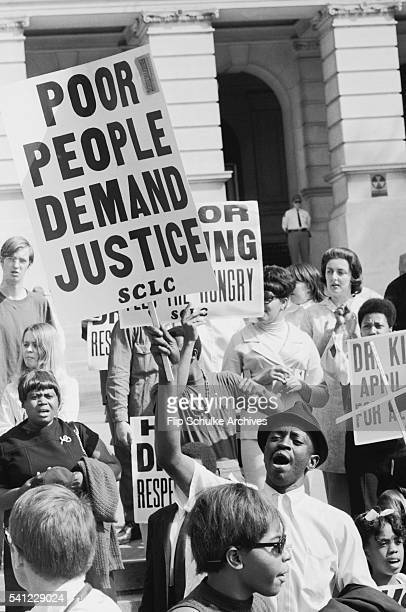 Civil rights activists carry picket signs on the steps of a government building during a rally
