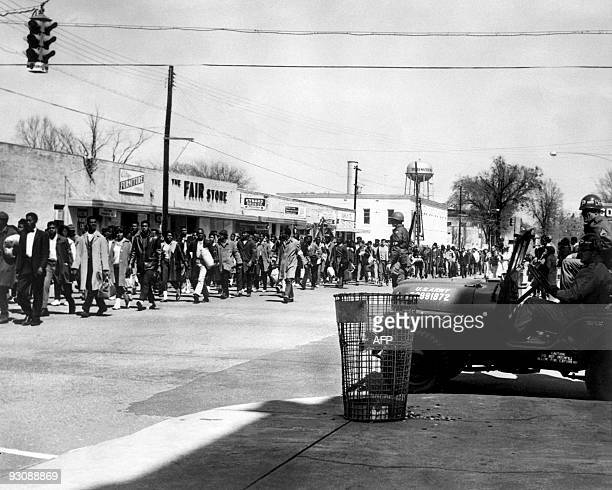 Civil rights demonstrators, led by Dr Martin Luther King, pass by federal guards as they make their way from Selma to Montgomery on March 23, 1965 in...
