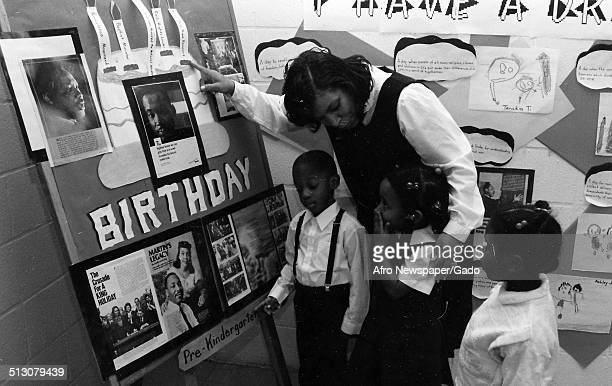 Civil Rights leader Coretta Scott King and children gesturing at a poster 1978