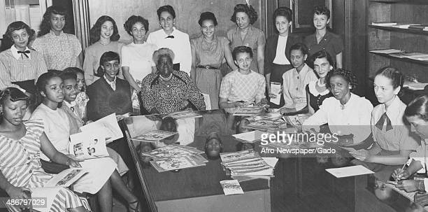 Civil rights leader Mary McLeod Bethune and other women seated around the table holding documents at a meeting of the African American advocacy and...