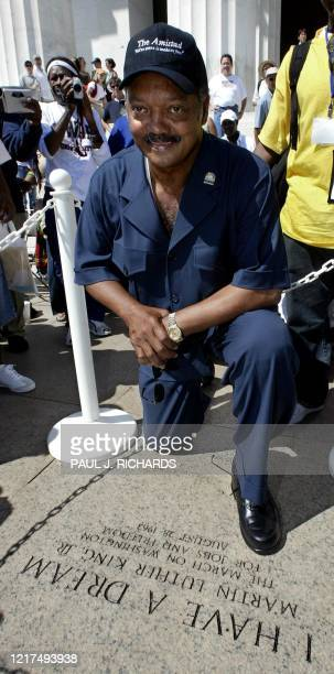 Civil Rights leader Rev Jesse Jackson poses for a photo atop the engraved granite plaque honoring Rev Dr Martin Luther King Jr 23 August 2003 on the...