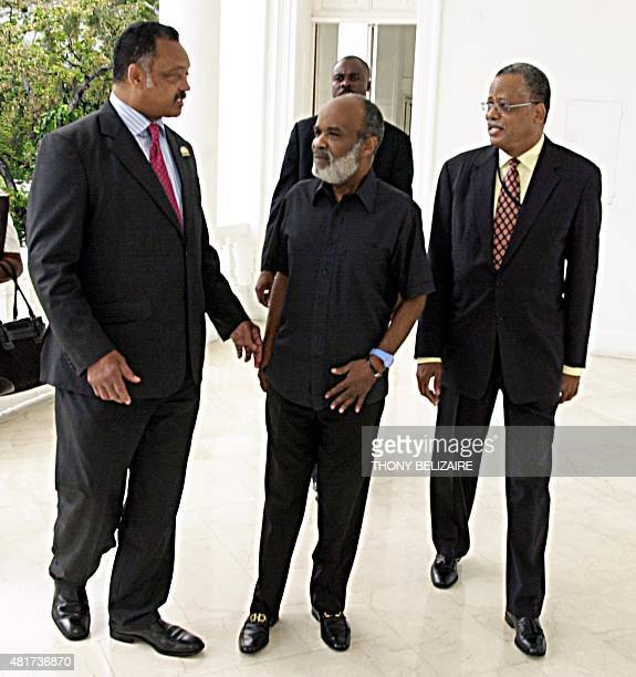 US civil rights leader Rev Jesse Jackson speaks with Haitian Foreign Minister Fritz Longchamps and President Rene Preval following a press conference...
