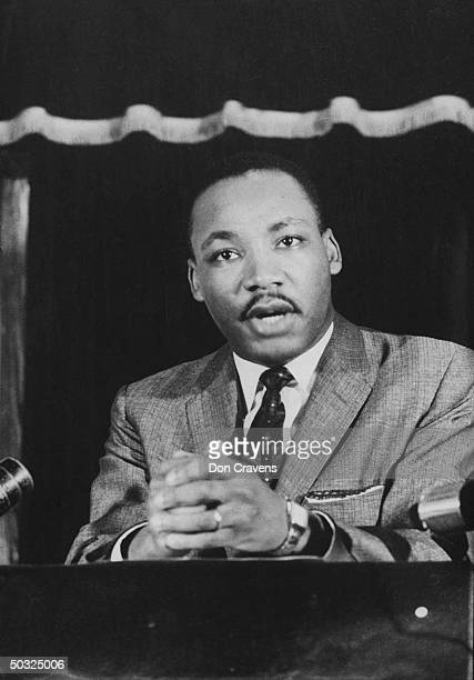 Civil rights leader Rev Martin Luther King speaking from pulpit at mass meeting abot principles of nonviolence before leading assembly to ride newly...