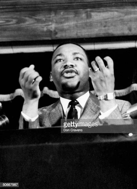 Civil rights leader Rev Martin Luther King speaking from pulpit at mass meeting about principles of nonviolence before leading assembly to ride newly...