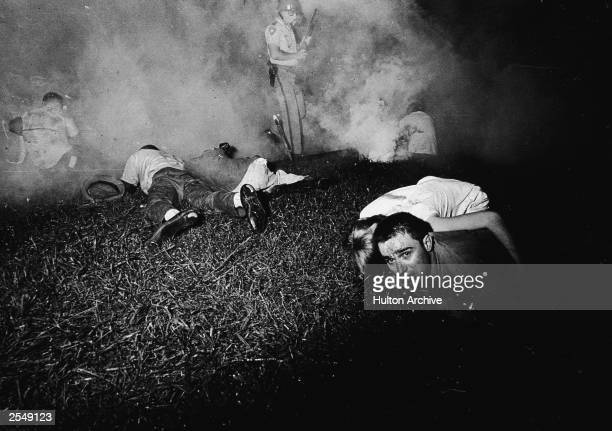 Civil rights marchers stay close to the ground as Mississippi Highway Patrolmen use tear gas on the protestors Canton Mississippi 1960s
