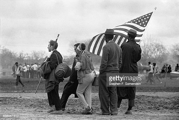 Several men and a woman civil rights marchers with large American flag on gathering on field of City of St Jude School preparing for the concluding...
