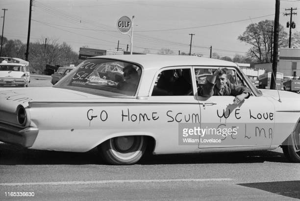 Civil Rights opponents, abroad a car with lettering 'Go Home Scum, We Love Selma' written on the side of the vehicle, drive near the peaceful...