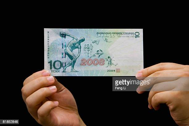 Civil servant of the People's Bank of China shows a commemorative bank note on July 8, 2008 in Beijing, China. The People's Bank of China , the...