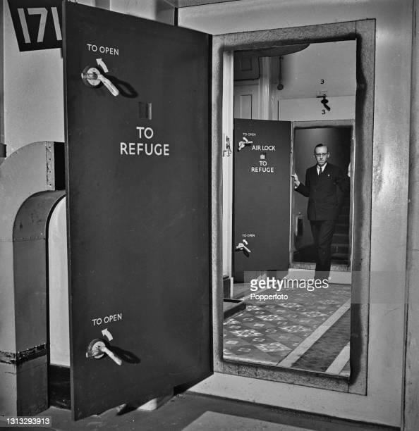 Civil servant walks through the air lock doors to the secure Air Raid Refuge at the Foreign Office in Whitehall, London during World War II in...