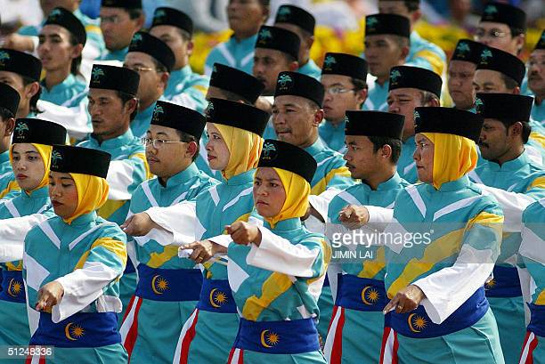 Civil servants march in a parade during the National Day celebrations in the eastern town of Kuantan 31 August 2004 Malaysia celebrated its 47th...