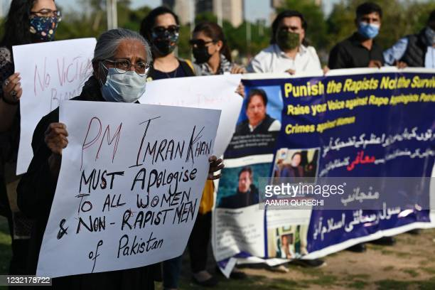 Civil Society activists hold placards during a protest against Pakistani Prime Minister Imran Khan's remarks blaming how women dress for a rise in...