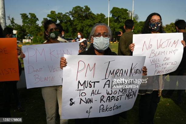 Civil Society activsts hold placards during a protest against Pakistani Prime Minister Imran Khan's remarks blaming how women dress for a rise in...