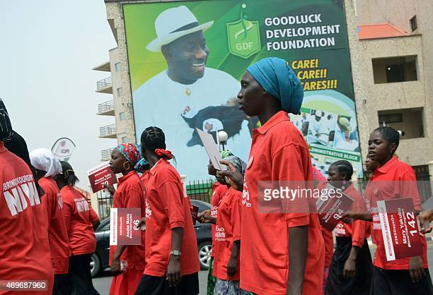 Civil society groups march past billboard of outgoing Nigerian President Goodluck Jonathan to press for the release of 219 schoolgirls abducted by...