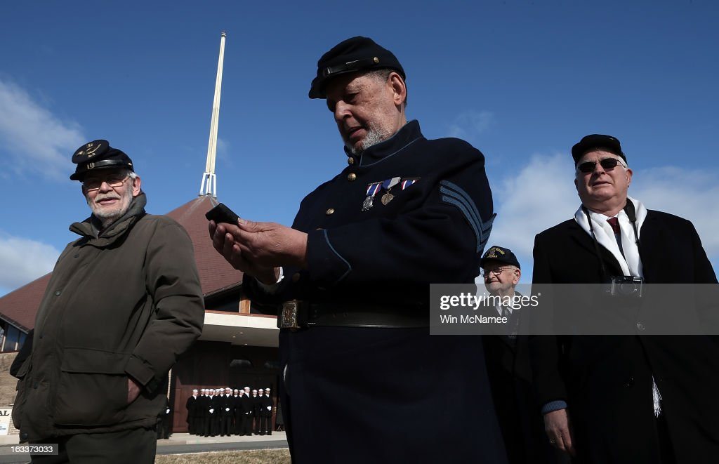 Civil War enthusiasts await the beginning of a funeral service at Arlington National Cemetery for two unknown sailors who were killed in 1862 when the Civil War era USS Monitor sank off the coast of North Carolina March 8, 2013 in Arlington, Virgiina. The sailors' remains, recovered when a portion of the ship was raised eleven years ago, were buried with full military honors.