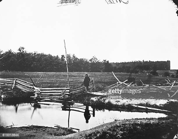 Civil War photographer Mathew Brady stands on the site of the Battle of Gettysburg, among pieces of a broken fence next to a pond, ca. 1863. |...
