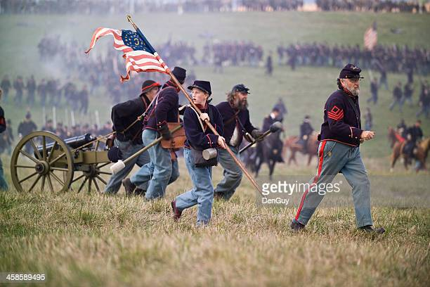 civil war reenactment soldiers running with artillery piece - reenactment stock photos and pictures